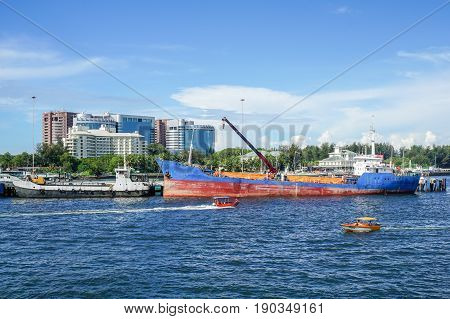 Labuan,Malaysia-May 26,2017:View of daily activities of Labuan port with vessels & background of Labuan town in Labuan,Malaysia.Labuan is an international financial centre & Malaysia only deep water anchorage