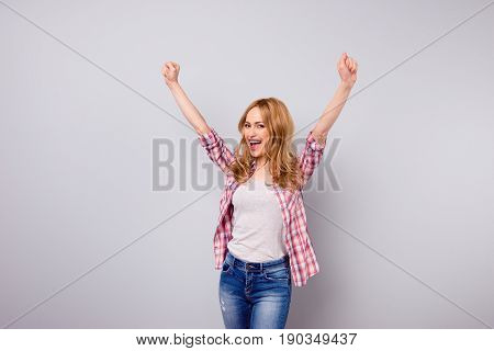 Cute Young Smiling Woman In Jeans And Checkered Shirt Triumphing With Raised Hands Against Gray Back
