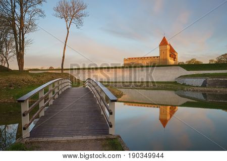 Kuressaare castle and bridge over the moat in beautiful sunrise light. Water with reflections