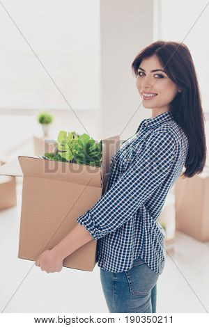 Successful Young Woman Is Moving To New Nice Place And Holding Box With Her Belongings. The Room Is