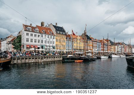 Copenhagen Denmark - August 11 2016: Nyhavn a cloudy day. It´s a 17th-century waterfront canal and entertainment district in Copenhagen lined by coloured townhouses it has many historical wooden ships.