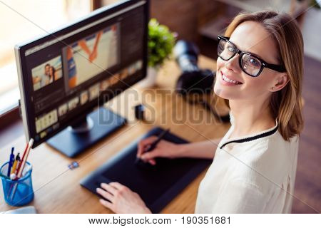 Top View Of Intelligent Blond Young Woman Working With Computer And Graphic Tablet, Stylus, Smiling.