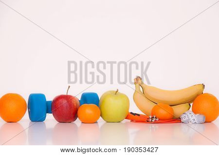 The concept of a healthy diet. Fintes meals. Sport lifestyle. Dumbbells. Oranges. Apples. Bananas. fruit juice. The skipping rope. Measuring tape waist. on a white background. studio shooting.