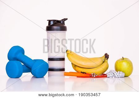 The concept of a healthy diet. Fintes meals. Sport lifestyle. Dumbbells. green apple. Bananas. shaker. The skipping rope. Measuring tape waist. on a white background