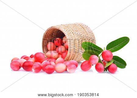 karanda or carunda tropical fruit in wooden basket with green leaves isolated on white background