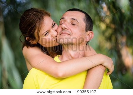 Affectionate father being hugged and kissed by her loving daughter