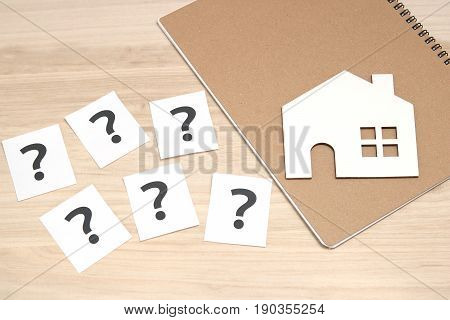 Miniature house and many question marks on white papers.   House with question marks and magnifying glass. Real Estate Concept.