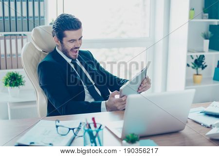 Cheerful Young Businessman Is Plying A Game On His Tablet In Office. He Is Very Excited, Wearing For