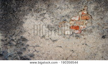 Old and dirty brick wall with damping plaster