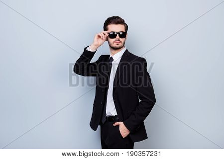 Young Handsome Brutal Man In Formal Clothes Holding Hand In Pocket And Touching His Sunglasses