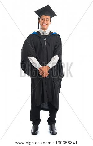 Full body happy Asian male university student in graduation gown smiling, isolated on white background. Good looking Southeast model.