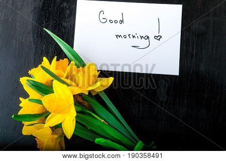 Bouquet Of Daffodil Near Card With Good Morning On Black Background. Top View. Copy Space. Mothers D