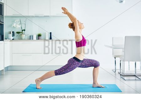 Portrait of fit red haired woman doing yoga exercises at home on floor: stretching muscles standing in warrior pose