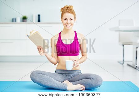 Portrait of fit red haired woman doing yoga exercises at home: reading book with smile  while sitting with legs crossed  in lotus position and looking at camera, smiling happily