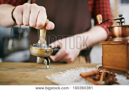 Closeup shot of barista working in coffee shop: pressing fresh grains with tamper after grinding them in antique mill