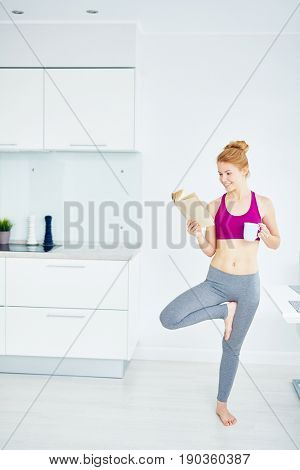 Portrait of fit red haired yogi woman doing exercises at home: standing in tree pose and reading book looking happy