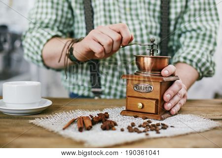 Closeup shot of man making cup of fresh black coffee, grinding beans with small wooden mill