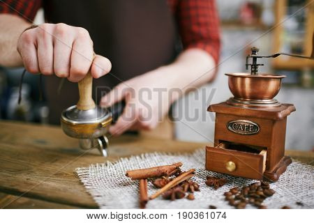 Closeup shot of barista working in coffee shop: pressing fresh grains with tamper, focus on antique grinder mill