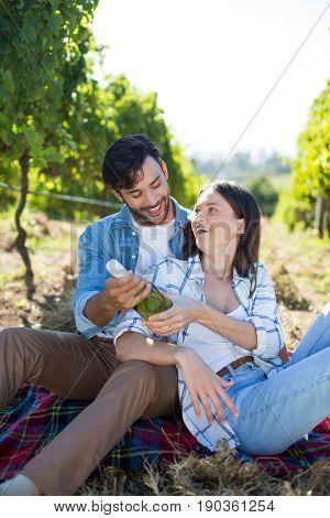Happy couple holding winebottle while sitting at vineyard