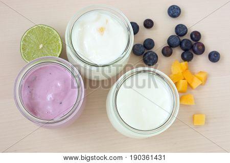 Three glass jars of yogurt: natural, with mango and blueberries.