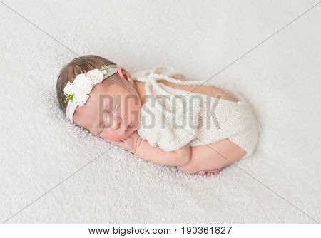 Cute infant sleeping wearing wonderful white warm suit with a cut on the back