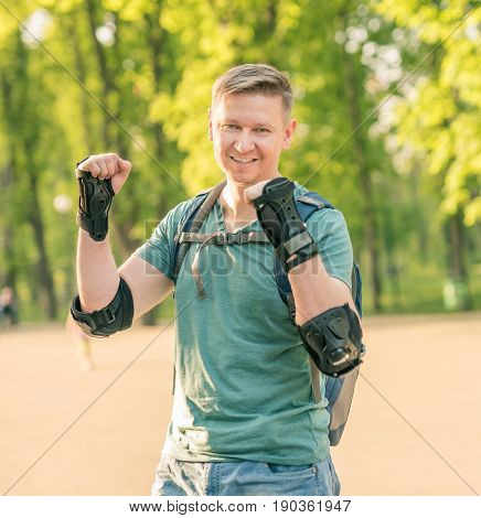 Handsome man wearing protection for active sport in green tshirt smiling, standing in the park