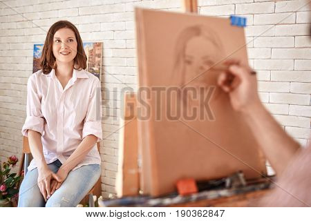 Portrait of artist drawing  portrait of beautiful young woman sitting in front of him in art studio, focus on smiling model