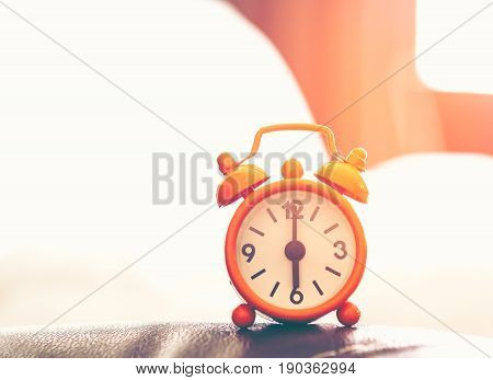 Alarm clock on bed in morning with sun light, vintage tone