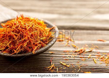 Spice saffron in a wooden spoon on the table. Close-up.