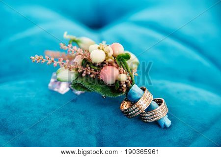 boutonniere with two wedding rings on blue background