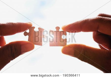 hands trying to couple puzzle piece with sunshine background. concept idea jigsaw and sunlight