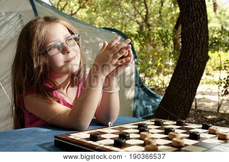Little girl playing draughts board outdoor (camping) in the sunny summer day. The touristic tent in background. Education summer active recreation and touristic concept.