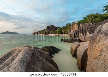 Beautifully shaped granite boulders and a dramatic sunset at picture perfect tropical Anse Source d'Argent beach, La Digue island, Seychelles.