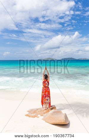 Traditinaly dressed asian tourist woman wearing long red floral summer dress doing yoga by sea on Anse Patates beach, La Digue Island, Seychelles. Summer vacations on picture perfect tropical island.