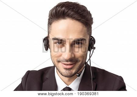Smiling young call center operator in headset looking at camera isolated on white
