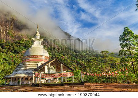 Buddist stupa with green mountains and blue sky on the way to the top of Adam's peak Sri Lanka