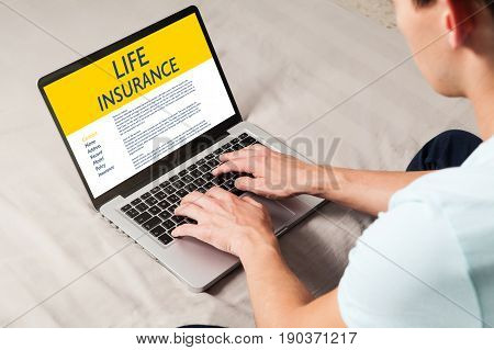 Life Insurance concept: Man typing in a laptop computer with Life Insurance contract in the screen