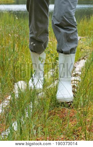 Galoshes woman going in rubber boots in a meadow