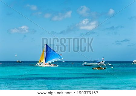 Sailing boat with blue and yellow sails in the tropical sea. a lot of different ships in the water. Philippines Boracay.