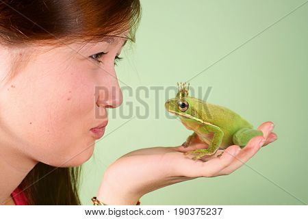 Teenage girl kissing Tree frog (Litoria infrafrenata) with a crown on his head