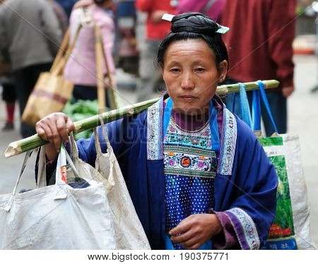 RONGJIANG CHINA - 13 NOVEMBER 2010: Chinese in the ethnic dress carrying the agricultural produce on the bamboo stick which is trying to sell in the city
