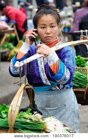 RONGJIANG CHINA - 13 NOVEMBER 2010: Chinese in the ethnic dress carrying the agricultural produce on the bamboo stick which is trying to sell in the city talking through the mobile phone