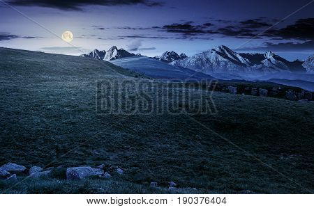 Hight Tatra mountain summer landscape at night in full moon light. meadow with huge stones among the grass on top of the hillside near the peak of mountain range