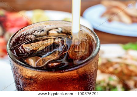 Cola in glass with ice cubes with food in the background.
