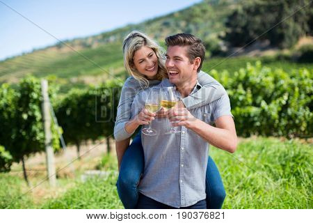 Portrait of happy young couple toasting wineglasses while piggybacking at vineyard