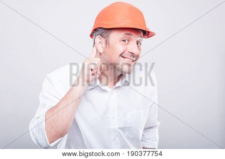 Portrait Of Contractor Wearing Hardhat Making Can't Hear Gesture