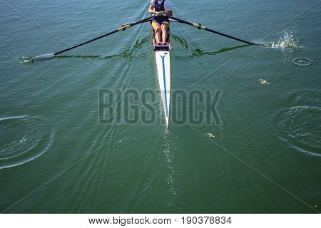 A young girl rowing in boat on water
