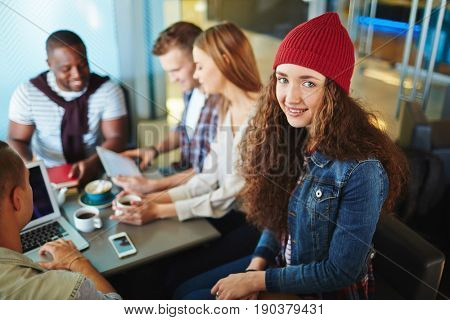 Pretty young manager in red knitted hat looking at camera with charming smile while her colleagues sitting at cafe table and having project discussion