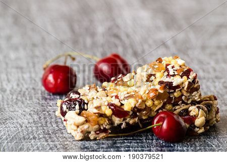Useful snack. Bars of muesli with cereals and fruits on a wooden background.