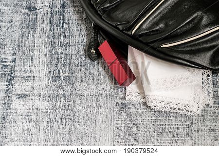 Women's accessories. A small black handbag, a white handkerchief with lace trim and a lipstick on a gray wooden background.